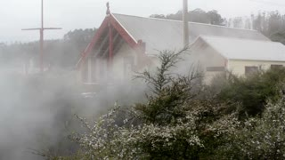 Maori village meeting house and steam from hot springs and thermal vents