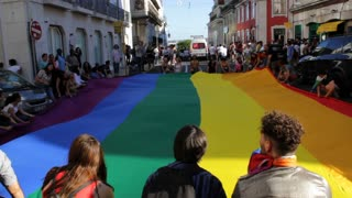 People hold a huge rainbow flag at LGBT Pride parade