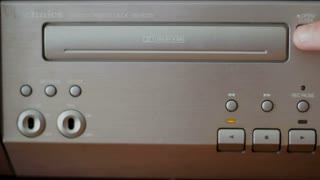 Putting a music cassette into a retro stereo player and pressing play