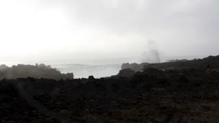 Volcanic coastline Landscape. Waves crashing against black volcanic rock formations
