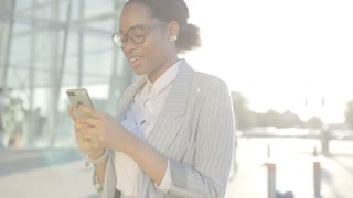 An excited and attractive woman is chatting on her Smartphone. Walking in the crowded place. Wearing Classical shirt, jacket. Looks successful and happy. Business Lifestyle.