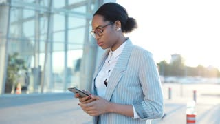 Attractive Afroamerican Businesswoman walking at the Breaking the City. Woman in Classical Suit and Glasses using her Mobile Phone for Social Network. Business Lifestyle. Successful People.
