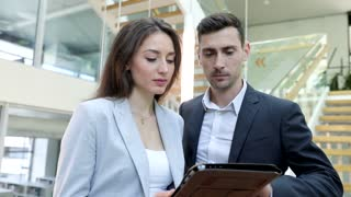 Attractive Business Woman Holding Digital Tablet. Discussing Business Ideas with Handsome Businessman. Standing in the Modern Glass Office. Informal Meeting in the Hall.