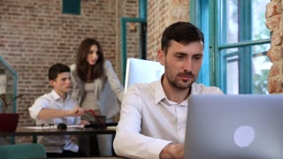 Attractive Businessman Working on his Modern Laptop. Making New Start up. Looking at the Screen. Couple of Business People Standing in the Background. Wall with Bricks. Slow Motion.