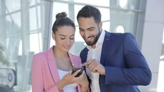 Attractive Businesswoman and Businessman Looking on Mobile Phone Together. People working on Mobile Application. Discussing New App and Smile. Startup Business People. Stylish Look.