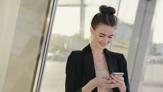 Attractive Businesswoman chatting on her Mobile Phone. Stylish hairstyle. Neat and Nice Dressed Woman. Looks Satisfied and Successful. Windy Weather.
