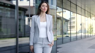 Attractive Businesswoman Walking in the Big Town. Wearing Stylish Classical Suit. Confident Gait. Big Modern Building in the Background. Successful Lifestyle. Neat Hairstyle.