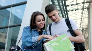 Attractive Man and Pretty Woman Travelling to Foreign City. Couple of two Young People Standing near the Airport. Holding Tourist Map. Having Backpacks. Woman pointing with her Finger.