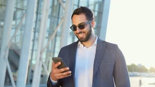 Attractive Multinational Businessman Working on his Smartphone. Man is walking in the City at Break and Texting Massage. Business Building on the Background. Classical Dressed in modern Sun Glasses.