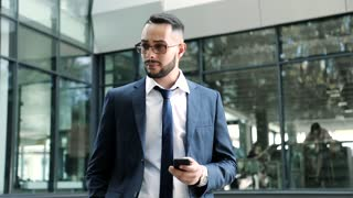 Attractive Successful Man Standing by the Modern Office Building. Looking Confident. Stylish Hairstyle. Wearing Classical Eyeglasses. Working on his Mobile Phone. Typing on it. Business Lifestyle.