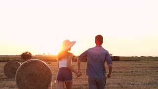Attractive Woman Holding Hands of her Beloved Man While Running on the Farm. Taking off her Straw Hat. People Enjoying Evening on the Harvested Field at Sunset. Romantic Evening Mood.