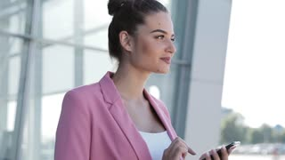 Attractive Woman Smiling and Actively Using Smartphone. Business Woman Communicating with her Friends while standing outside the Business Center. Browsing the Internet, Female Portrait.