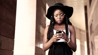 Attractive Young Afro-American Woman Using her Mobile Phone. Working on it. Looking at her Golden Wristwatch. Wearing Eyeglasses, Black nice Hat. Stylishly Dressed.
