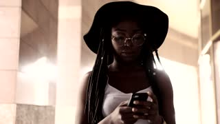 Attractive Young Afro-American Woman Walking in th Big City. Using her Smartphone. Looking Seriously on it. Stylish Outfit. Afro Hairstyle. Wearing Round Eye Glasses.