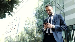 Attractive Young Businessman Using his Mobile Phone. Getting Good News on Mail. Successful Business Project. Stylish Positive Man. Pleasant Mood. Wearing Black Classic Suit. Multi ethnic People.