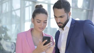 Attractive Young Businesspeople Looking on Mobile Phone Together. People working on Mobile Application near Office Building. Discussing Daily Business Plans. Startup Business People. Classical Suit.