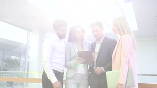 Attractive Young Businesswoman Explaining her Business Idea to the Collegues. Using Modern Digital Tablet. Business People Standing Indoor the Office Building. Business Partners.