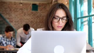 Attractive Young Businesswoman Wearing Eyeglasses. Working on his Computer at the Table. Looking Successful. Thinking about Business Projects. Business People Discussing Charts and Graphs.