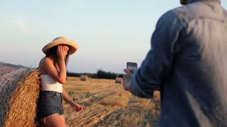 Attractive Young Girl Standing on the Farm Leaning on Round Bale of Hay. Posing on Camera. Man Holding Mobile Phone. Taking a Photo of Beautiful Woman. People Enjoying on the Harvested Field.