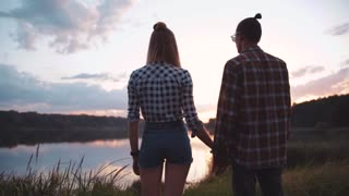 Back view of Attractive Young People in casual outfit standing by the lakeside, Holding Their Hands, looking at each other, enjoying the scenery. Romantic Date, Relationship Goals. Happy Together.