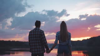 Back view of Young People in Love standing by the lakeside, Holding their Hands. Romantic atmosphere, relationship goals. Beautiful Lake, orange Summer Sunset on the background.