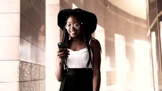 Beautiful Afro-American Young Woman Walking in the City. Using her Smartphone, Social Networks. Stylishly Dresses. Wearing Cool Eyeglasses, Black Hat. Afro Hairstyle.