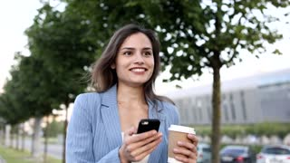 Beautiful Young Businesswoman Wearing Official Jacket. Walking in the Streets During the Break. Holding Delicious Coffee, Modern Mobile Phone. Nice Weather Outside. Business Lifestyle.