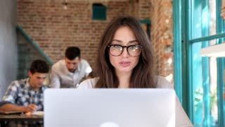 Beautiful Young Woman Working in the Office. Sitting at the Table. Looking on Camera. Charming Smile. Attractive Girl Wearing Eyeglasses. Creative Collegues Discussing Ideas in the Background. Start up.
