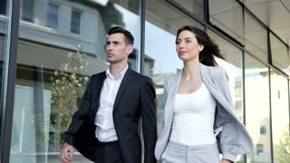 Business Partners Walking near Glass Office Building. Informal Meeting During Break. Successful Business Collegues. People Wearing Classical Suits. Confident Gait. Serious Office Workers.
