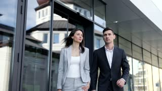 Business People Exiting the Office. Businesswoman Looking Pretty, Stylish. Successful and Confident Businessman. Office Workers. Business Partners Walking Together. Classical Suits.