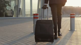 Businessman is Late for a Airplane. Handsome young Afro-American in a formal Suit pulls a Suitcase, checks the Time, hurries on in a bright Sunlight. Business Trip, Time Saving, Business Meeting.