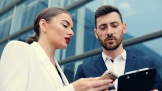 Businesswoman and Businessman working on Phone using Mobile App and talking. Working Concentrating. Business Building at the Background. Classical Dressed. Successful People. Business Partners.