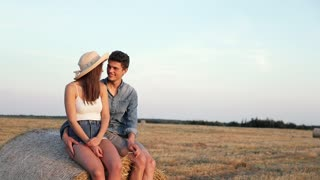 Casually Dressed Couple Sitting on the Bale of Hay on the Farm. Hugging Sincerly Each Other. Loving People Having Meeting Outside. Enjoying Time on the Harvested Field. Summer Sunset.
