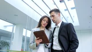 Charming Businesswoman Standing with Handsome Businessman Indoor the Office . Talking about Successful Business Ideas. Young Woman Explaining Project to her Collegue. Informal Meeting.