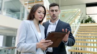 Charming Young Businesswoman Holding Modern Digital Tablet in her Hands. Businessman Explaining something on it. Collegues Standing at the Ofiice Building. Having Informal Meeting.