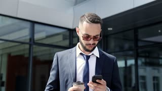 Classically Dressed Young Man Walking near the Office. Using Cellphone. Sliding on his Smartphone's Screen. Looking around. Holding a cup of Coffee in his Hands. Business Lifestyle. Multiethnic.