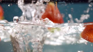 Close up of Fresh Strawberries Falling one by one into the Water. Plate with Crystal clear Water. Splashing Water. Sweet Fruits. Slow Motion. Series of Shots about Strawberries