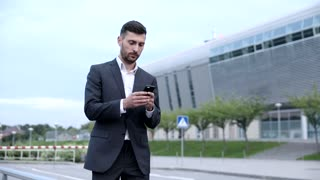 Close up of Handsome Businessman Walking in the Street. Pleasant Mood. Nice Day. Man Using Mobile Phone. Wearing Official Suit. Business Lifestyle. Stylish Hairstyle.
