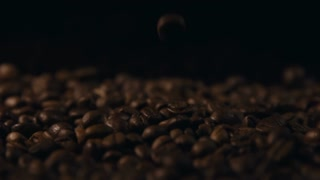 Close Up Viev of Coffee Beans Fall. Slow motion. Coffe Production. Coffee on dark background. Coffee in Breakfast.