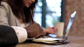 Close up view of Afroamerican Businessman's Hand Holding Pencil in his Fingers. Making Notes ini his Notebook. Writing some Information. Young Woman Typing on her Keyboard in the Background.