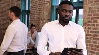 Close up view of Attractive Afroamerican Businessman. Holding Office Tablet with Papers. Wearing Classical White Shirt. Business People in the Background. Charming Smile. Slow Motion.