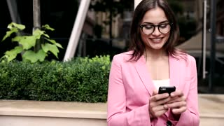 Close up view of Attractive Professional Businesswoman. Standing in front of the Office Building. Cars reflect in the Glass Building. Girl Typing on her Smartphone. Wearing Eyeglasses.