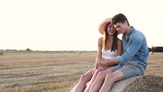 Close up view of Attrective Couple Sitting on Round Bales of Hay. Happy People Hugging Each Other. Spending Time Together. Enjoying Life. Farm Style. Summer Outfit. Enchanting Nature.