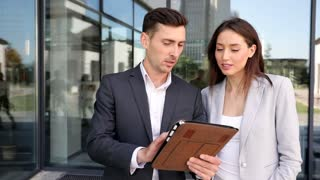 Close up view of Business People Standing by the Office Building. Talking about Serious Deal. Informal Meeting. Businessman Using Digital Tablet. Pretty Businesswoman Wearing Classical Suit.
