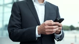 Close up view of Businessman's Hands Typing on Mobile Phone. Handsome Man Holding Modern Device in his Hands. Looking Satisfied. Smiling Sincerly. Portrait of Handsome Man.