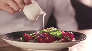 Close Up View of Chef is finishing Delicious Salat with Sauce in Slow Motion. Chef finishing Tasty Dish with Pepper, Salt , Herbs, Mustard. Fast Food. Chefs Restaurant. Delicious Food.