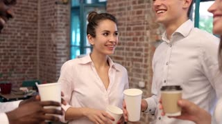 Close up view of Group of Businessman Standing in the Office. Informal Meeting to Celebrate Sucessful Deal. Business Partners Having Fun. Young Woman Drinking Tasty Coffee from Paper Cup.