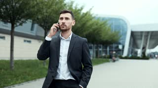 Close up view of Male Office Worker Walking in the City. Speaking on Mobile Phone. Looking Confident and Successful. Having Serious Talk. Elegant Suit. Bearded Handsome Businessman.