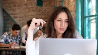 Close up view of Pretty Businesswoman Sitting at the Table in the Office. Modern Interior. Young Woman Putting on her Eyeglasses. Office Workers Having Informal Meeting in the Background.