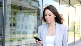 Close up view of Pretty Businesswoman Walking in the City. Using her Smartphone. Taking a Walk near Huge Building. Classically Dressed. Confident Gait. Looking Serious.